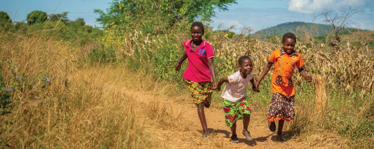 A group of children running together in the fields