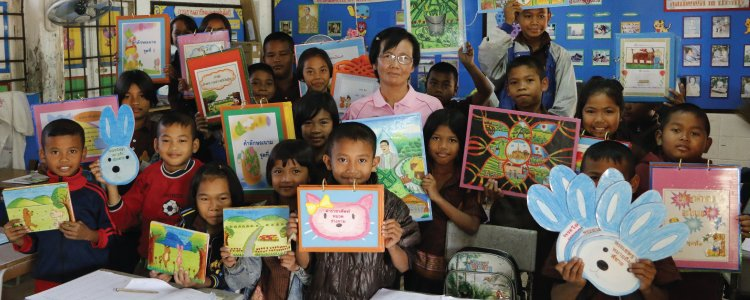 A class of students proudly showing their art work in one of the schools in Thailand AP.
