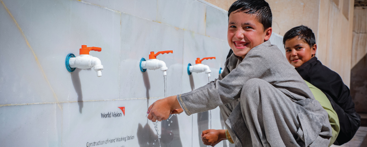 Two boys washing their hands at the newly installed Hand Washing Station
