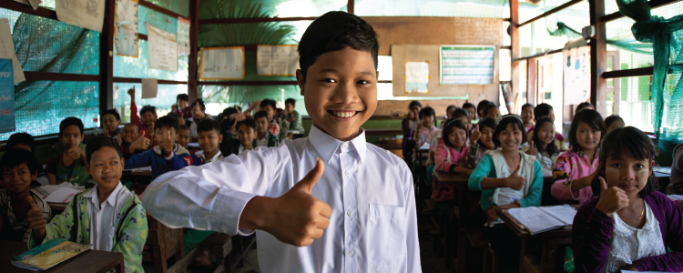 School students posing with thumbs up pose. Boy standing in front with thumbs up.